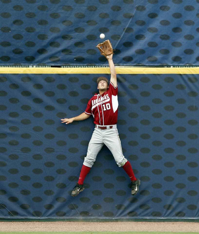 Photo - Arkansas' Joe Serrano (10) catches a would be home run by LSU's Alex Bregman for an out during the sixth inning at the Southeastern Conference NCAA college baseball tournament on Saturday, May 24, 2014, in Hoover, Ala. (AP Photo/Butch Dill)