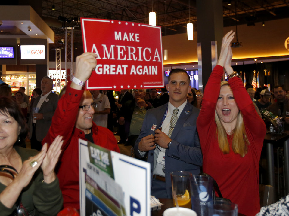 Photo - Seth Evetts, left, and Sarah Williams cheer  as Republican Party backers gathered Tuesday night at Main Event Entertainment in northwest Oklahoma City as election returns rolled in the presidential race against Donald Trump and Democrat Hillary Clinton. Oklahomans on Tuesday also cast votes on several state ballot measures, a host of legislative contests and other local issues and offices. Photo by Bryan Terry, The Oklahoman