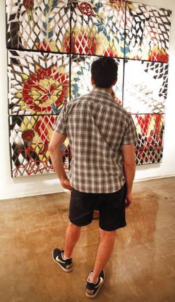 """Photo -  Jason Willaford, a Dallas artist, looks over one of the pieces in his show """"Vinyl Exposed."""""""