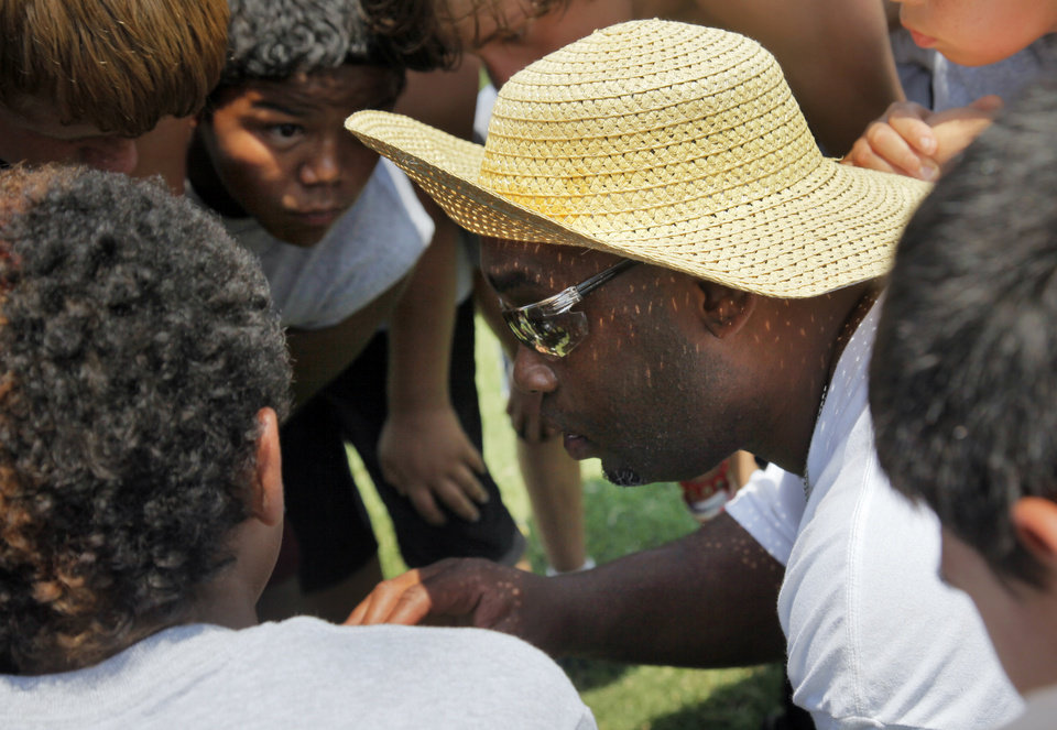 Photo - Former OU quarterback Jamelle Holieway gives campers a play to run during Holieway's Spirit of Oklahoma football camp in Weleetka, Okla., Friday, July 6, 2012. Photo by Nate Billings, The Oklahoman