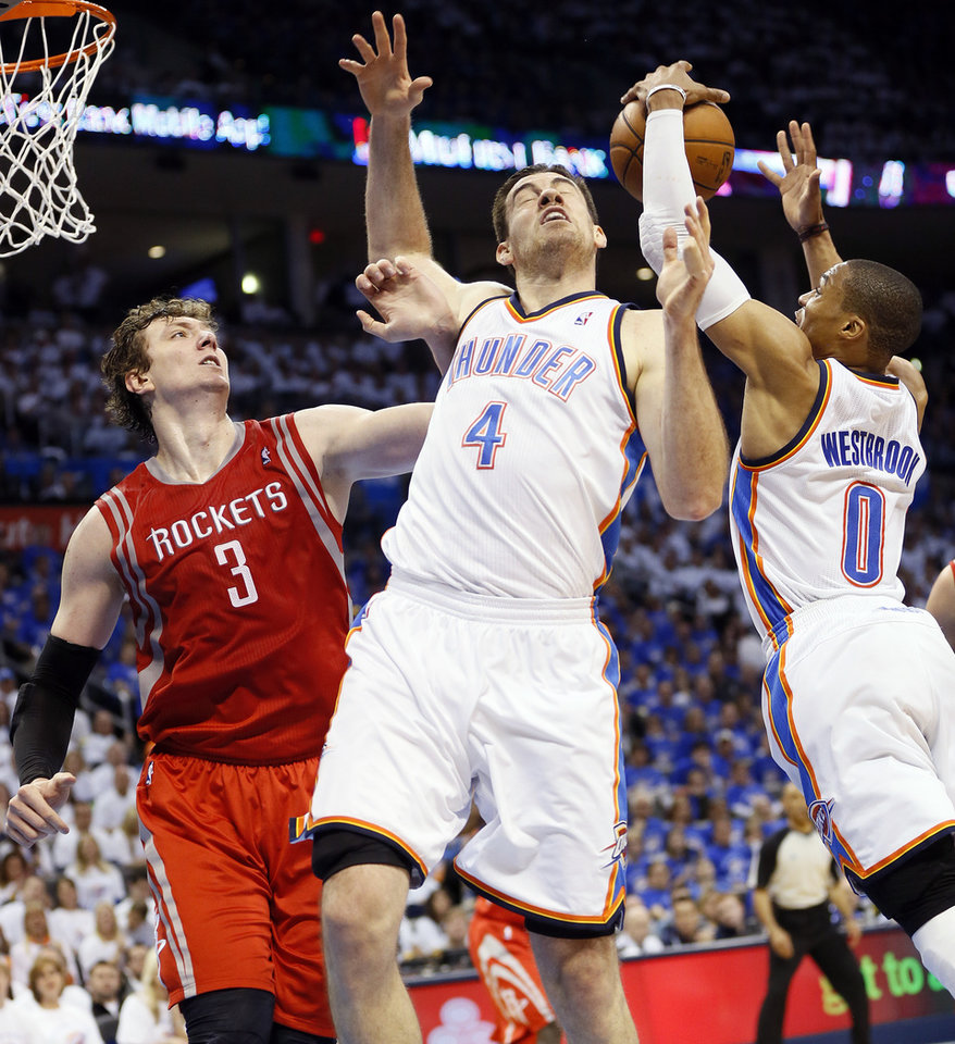 Oklahoma City\'s Russell Westbrook (0) rebounds the ball as Nick Collison (4) collides with Houston\'s Omer Asik (3) during Game 2 in the first round of the NBA playoffs between the Oklahoma City Thunder and the Houston Rockets at Chesapeake Energy Arena in Oklahoma City, Wednesday, April 24, 2013. Oklahoma City won, 105-102. Photo by Nate Billings, The Oklahoman