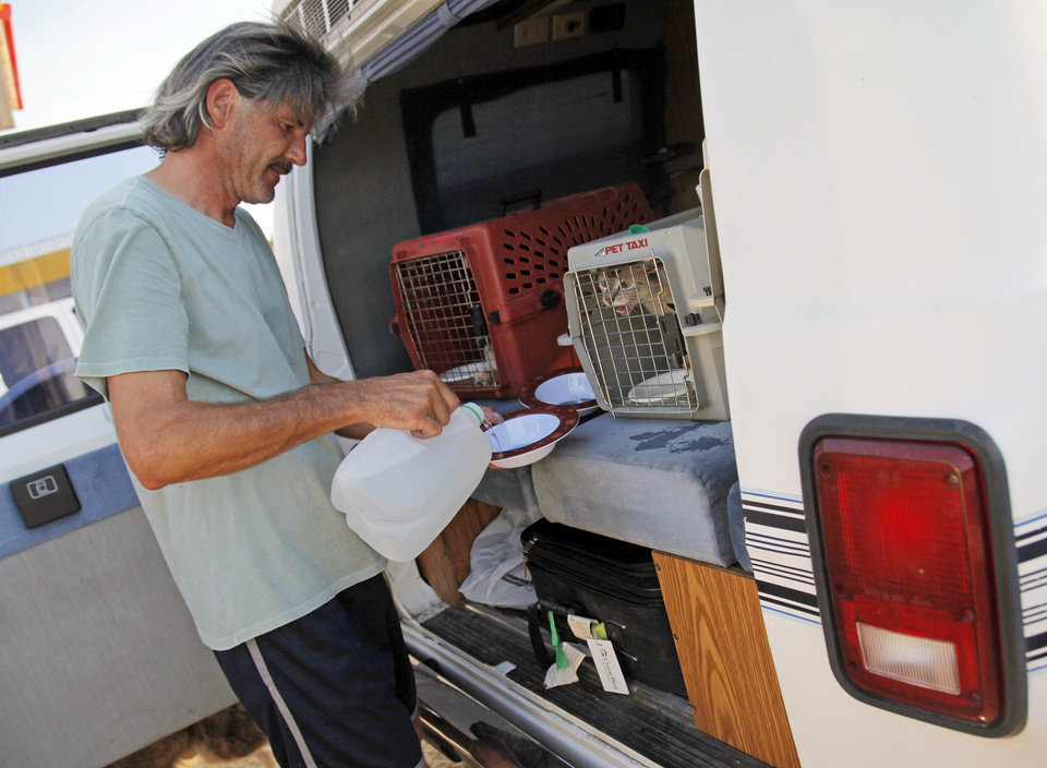 Photo - Vin Bayne pours water for his pets while waiting at a gas station at Hwy 9 and SE 108 Ave. after evacuating his home as a wildfire burns through Cleveland County near Norman, Okla., Friday, Aug. 3, 2012. Vin Bayne and his wife Polly Bayne evacuated their home off of SE 132nd with their 4 cats and 2 dogs. Photo by Nate Billings, The Oklahoman