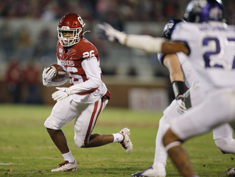 Photo - Oklahoma's Kennedy Brooks (26) carries the ball during an NCAA football game between the University of Oklahoma Sooners (OU) and the TCU Horned Frogs at Gaylord Family-Oklahoma Memorial Stadium in Norman, Okla., Saturday, Nov. 23, 2019. Oklahoma won 28-24. [Bryan Terry/The Oklahoman]