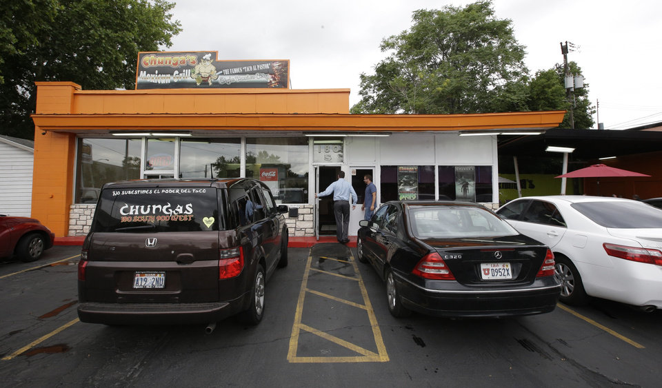 Photo - In this July 29, 2014, photo, patrons enter the Chunga's Mexican Grill, in Salt Lake City. The hunt for a taste of Mexico City brings diners near a highway overpass in a neighborhood known for tire shops and tacos. (AP Photo/Rick Bowmer)