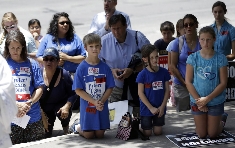 Photo - Anti-abortion supporters pray outside the Texas Capitol as the Texas House  debates HB 2, a bill that will place restrictions on abortion in the state, Tuesday, July 9, 2013, in Austin, Texas. (AP Photo/Eric Gay)