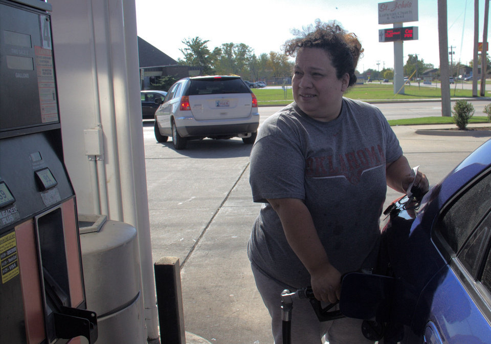 Paula Linares fills her car for $2.99 a gallon at the 7-Eleven at NW12th and Santa Fe in Moore. The average price of gasoline in Oklahoma City has dropped 50 cents over the past month. <strong>Adam Wilmoth - photo by</strong>