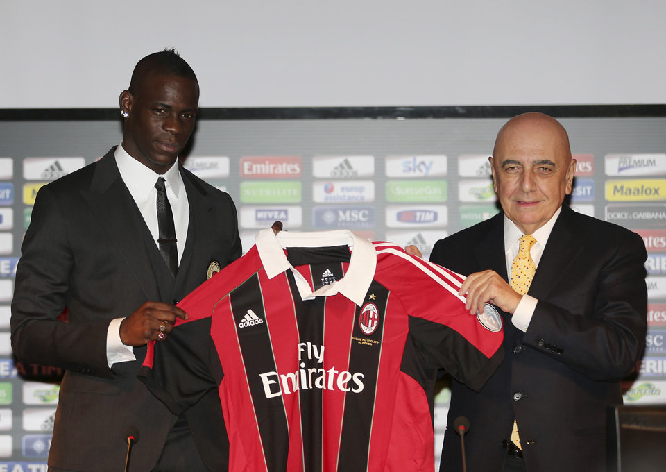 Italian striker Mario Balotelli, left, poses with AC Milan vice president Adriano Galliani and his new AC Milan jersey during an official presentation at the San Siro stadium in Milan, Italy, Friday, Feb. 1, 2013. Balotelli is expected to make his official debut for the Rossoneri against Udinese after his move from Manchester City. Balotelli finalised a �20 million transfer returning to Italy after a turbulent 2 1/2 years in the Premier League. (AP photo/Antonio Calanni) (AP Photo/Antonio Calanni)
