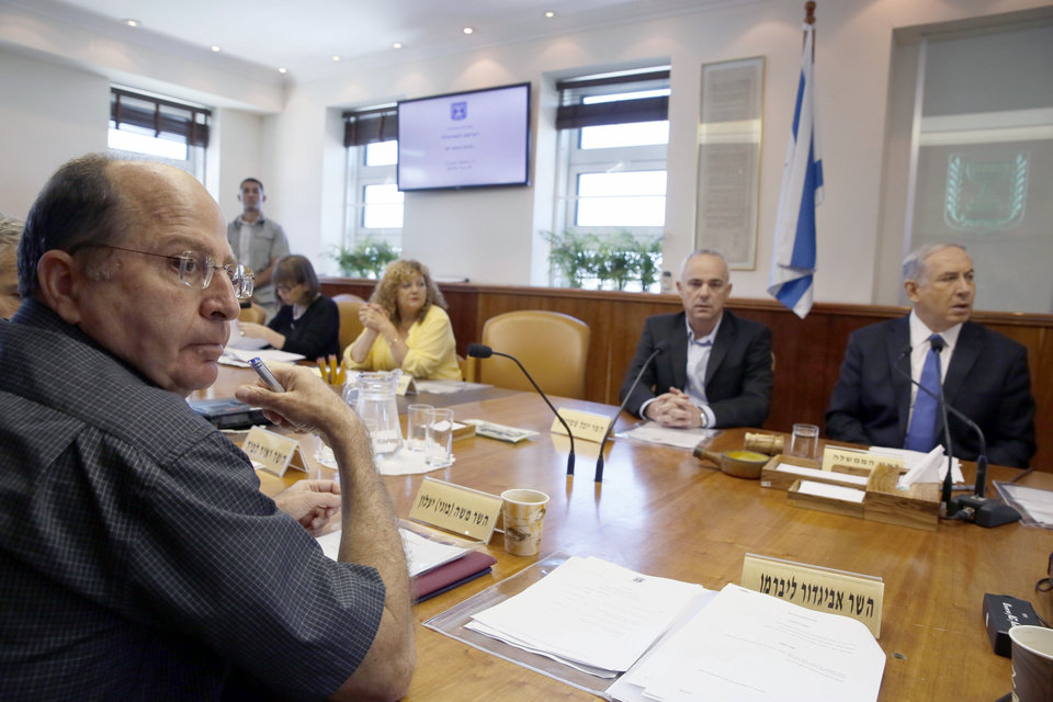 Photo - Israeli Defense Minister, Moshe Ya'alon, left, and other ministers attend the weekly cabinet meeting chaired by Israeli Prime Minister Benjamin Netanyahu, right, in the prime minister's office in Jerusalem, Sunday, July 6, 2014. Prime Minister Benjamin Netanyahu on Sunday said Israel would act calmly and responsibly in the face of rising Israeli-Palestinian hostilities, just hours after Israel's military carried out airstrikes on 10 sites in the Gaza Strip. (AP Photo/Gali Tibbon, Pool)