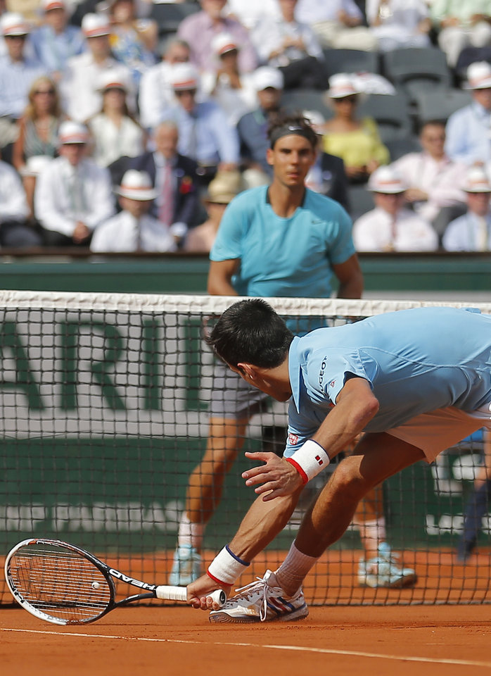 Photo - Serbia's Novak Djokovic returns the ball during the final of the French Open tennis tournament against Spain's Rafael Nadal, rear, at the Roland Garros stadium, in Paris, France, Sunday, June 8, 2014.  (AP Photo/Michel Spingler)