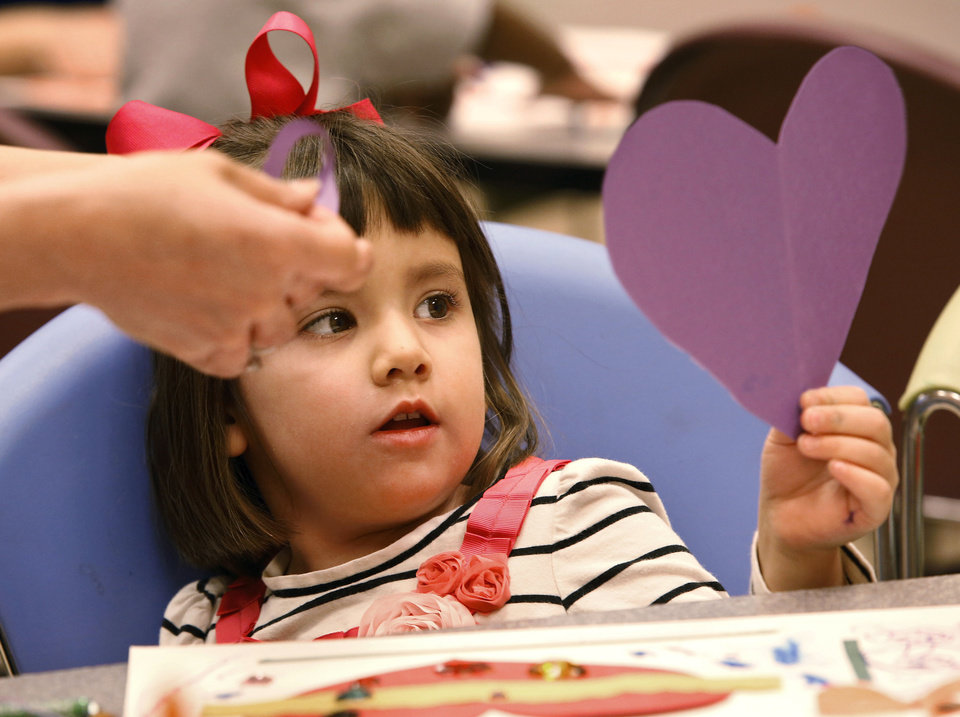 Ella Alexander, 4, looks at a heart cut from a piece of construction paper as she and her mom, Lydia Alexander, work on her art project.