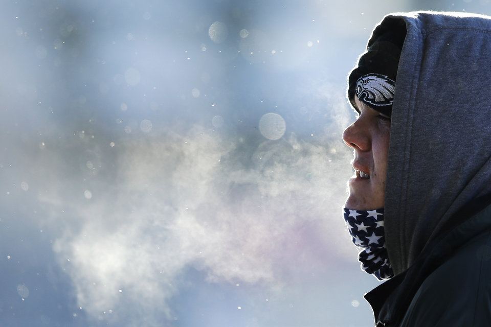 Photo - A commuter exhales in freezing tempters in the aftermath of a snowstorm Wednesday, Jan. 22, 2014, in Philadelphia.  A winter storm stretched from Kentucky to New England and hit hardest along the heavily populated Interstate 95 corridor between Philadelphia and Boston.   (AP Photo/Matt Rourke)