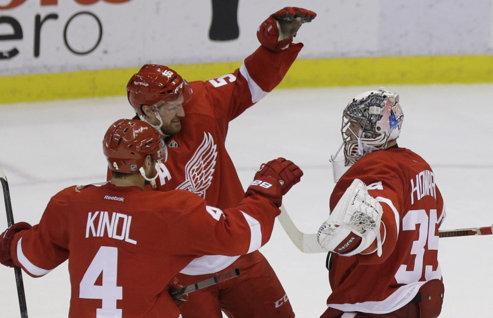 Photo - Detroit Red Wings goalie Jimmy Howard (35) is congratulated by Jakub Kindl (4), of the Czech Republic, and Niklas Kronwall (55), of Sweden, after Detroit's 4-3 win over the Washington Capitals in a shootout in an NHL hockey game in Detroit, Friday, Jan. 31, 2014. (AP Photo/Carlos Osorio)