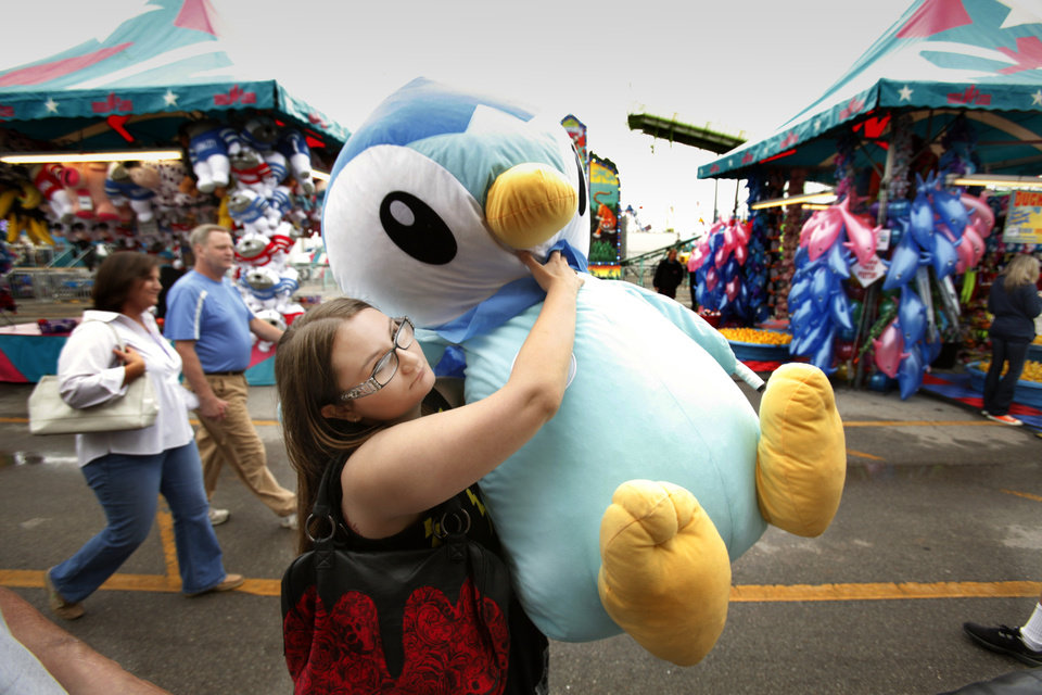 Photo - Desiree Bivins, 23 from Oklahoma City, carries the prize she won at the Wacky Wire game on the midway of the 106th Oklahoma State Fair at State Fair Park on Saturday, Sept. 15, 2012, in Oklahoma City, Okla.  Photo by Steve Sisney, The Oklahoman