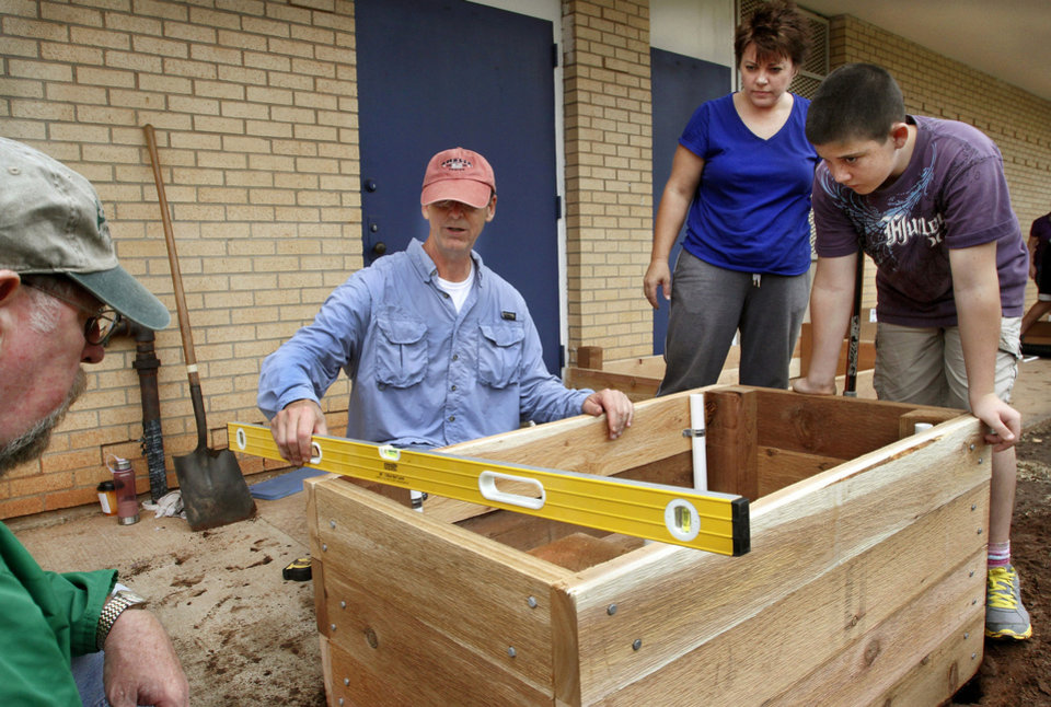 Principal Ruthie Rayner and her son, Ben, watch Bob Eichenberg check the level of a planter box before they permanently place it in the courtyard of the school. Eichenberg is a volunteer from Crossings Community Church. Volunteers are planting a garden at Stanley Hupfeld Academy.