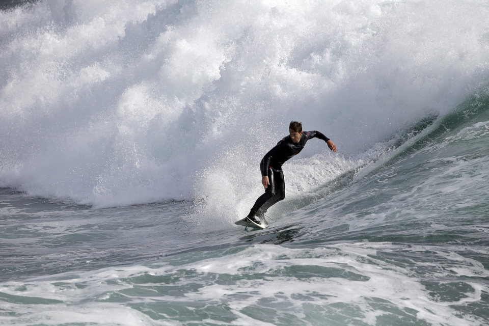 Photo - A surfer rides a bigger than normal wave caused by a storm off Steamer's Lane, a popular surf spot, Thursday, Dec. 10, 2015, in Santa Cruz , Calif.  A storm system is expected this afternoon, bringing rain to the Bay Area. (AP Photo/Marcio Jose Sanchez)