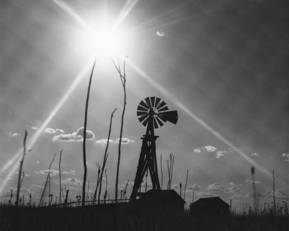 A relentless sun bears down upon drought-ridden southwest Oklahoma. A windmill surrounded by lifeless weed stalks and framed by sunrays produces a wild sort of beauty, perhaps the drought's only defense.  STAFF PHOTO BY PAUL LONG, THE OKLAHOMAN (1970)
