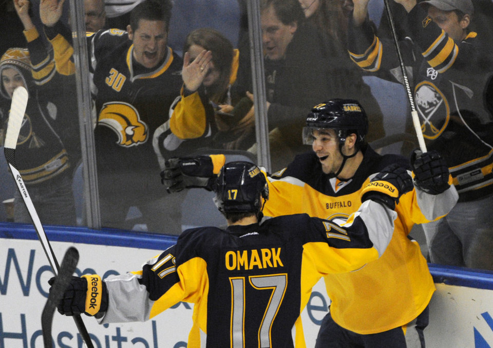 Photo - Buffalo Sabres' Linus Omark (17) celebrates the game-winning goal by Matt D'Agostini, right, during the third period of an NHL hockey game against the New Jersey Devils in Buffalo, N.Y., Saturday, Jan. 4, 2014. Buffalo won 2-1. (AP Photo/Gary Wiepert)