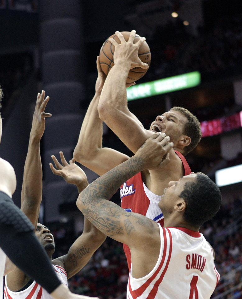 Photo - Los Angeles Clippers forward Blake Griffin (32) drives to the basket over Houston Rockets forward Greg Smith (4) during the first half of an NBA basketball game Saturday, March 30, 2013, in Houston. (AP Photo/Bob Levey)