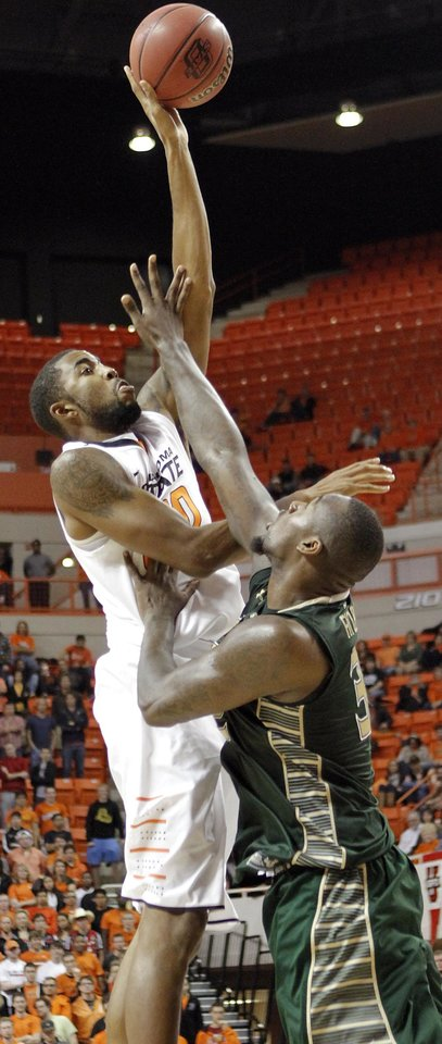 Oklahoma State \'s Michael Cobbins (20) puts a shot over South Florida Bulls\' Toarlyn Fitzpatrick (32) during the college basketball game between Oklahoma State University (OSU) and the University of South Florida (USF) on Wednesday , Dec. 5, 2012, in Stillwater, Okla. Photo by Chris Landsberger, The Oklahoman