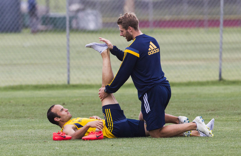 Photo - Los Angeles Galaxy forward Landon Donovan is assisted in stretching by trainer Kurt Andrews during a training session at StubHub Center in Carson, Calif., Saturday, May 24, 2014. Donovan, the most accomplished American player in the history of men's soccer, won't be going to his fourth World Cup. The 32-year-old attacker was among seven players cut Thursday when coach Jurgen Klinsmann got down to the 23-man limit well before the June 2 deadline. (AP Photo/Ringo H.W. Chiu)