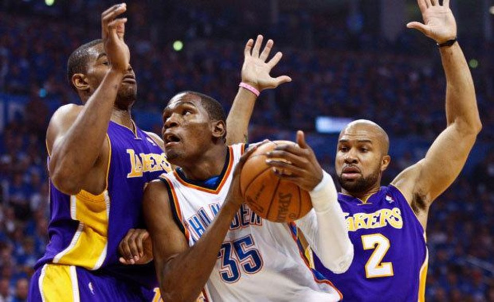 Oklahoma City Thunder forward Kevin Durant, center, drives to the basket in front of Los Angeles Lakers guard Derek Fisher, right, and center Andrew Bynum, left, in the first quarter of Game 3 of a first-round NBA basketball playoff series in Oklahoma City, Thursday, April 22, 2010. (AP Photo/Alonzo Adams)