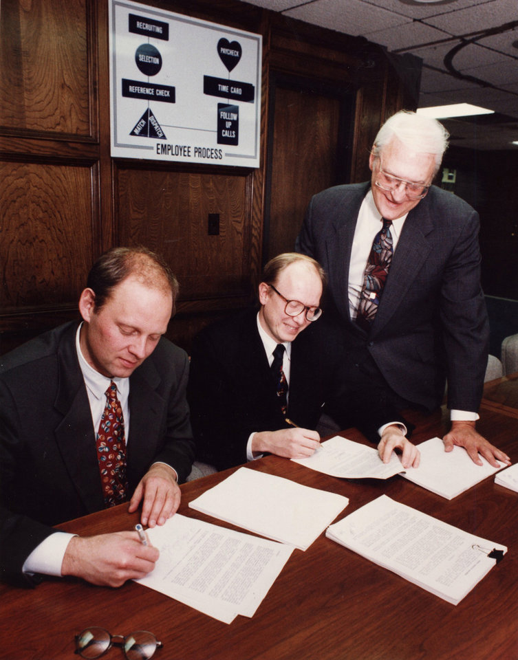 Photo -  Oklahoma City businessman Bob Funk, owner of Express Personel Services. ORIGINAL CAPTION: Robert A. Funk, right, president and chairman of Express Services Temporary and Permanent Personnel in Oklahoma City, watches as Lars Nurman, left, and Mike Haglind, of Sweden's largest temporary help firm, Teamwork, sign an agreement to operate a temporary help business in that Eurpoean country in 1992. [Photo by David McDaniel,  OKLAHOMAN ARCHIVES.]