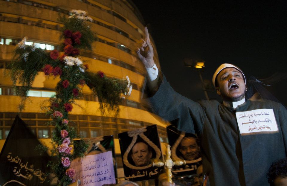 Photo -   An Egyptian Muslim cleric chants anti-Muslim Brotherhood slogans as he stands next to a cross made of flowers during a march marking the first anniversary of the victims who were killed during clashes with the military police in front of the National State T.V. building, known as Maspero, in Cairo, Egypt, Tuesday, Oct. 9, 2012. Muslim clerics, Christian priests, activists and former liberal lawmakers were among those marching to mark the anniversary of the