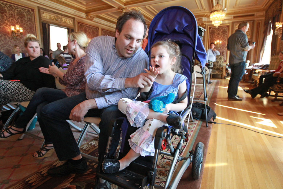 Photo - FILE - In this March 25, 2014, file photo, Clinton Atwater, left, plays with his daughter Asia Skye Atwater, 7, before the H.B 105 bill signing ceremony at the Utah State Capitol,  in Salt Lake City. Utah will begin issuing registration cards Tuesday, July 8, 2014, for its limited medical marijuana program targeting adults and children with severe epilepsy. (AP Photo/Rick Bowmer, File)