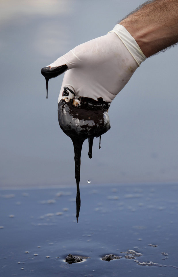 Photo - FILE - In this June 15, 2010 file photo, a member of Louisiana Gov. Bobby Jindal's staff wearing a glove reaches into thick oil on the surface of the northern regions of Barataria Bay in Plaquemines Parish, La. U.S. District Judge Carl Barbier ruled Thursday, Sept. 4, 2014, in New Orleans, La., that BP acted recklessly and bears most of the responsibility for the oil spill. The ruling exposes BP to about $18 million in civil fines under the Clean Water Act. (AP Photo/Gerald Herbert, File)