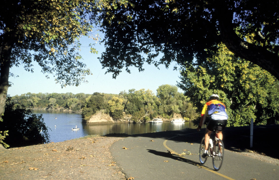 Photo - This undated photo provided by the Sacramento Convention & Visitors Bureau shows the American River Parkway in Sacramento, Calif. The wide trail is great for cyclists, runners and hikers, with countless dirt trails along the river for horseback riding and mountain biking.  It's one of many free things to see and do in Sacramento.    (AP Photo/Sacramento Convention & Visitors Bureau)