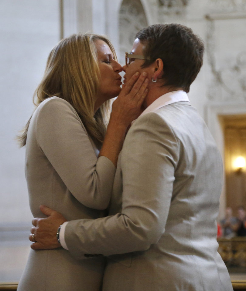Photo - Sandy Stier, left, kisses Kris Perry after they were wed by California Attorney General Kamala Harris at City Hall in San Francisco, Friday, June 28, 2013. Stier and Perry, the lead plaintiffs in the U.S. Supreme Court case that overturned California's same-sex marriage ban, tied the knot about an hour after a federal appeals court freed same-sex couples to obtain marriage licenses for the first time in 4 1/2 years. (AP Photo/Marcio Jose Sanchez)
