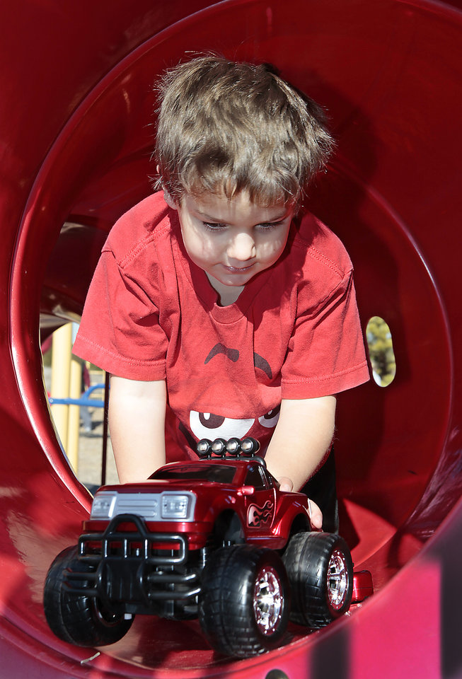 Nathan Cast, 6, plays with a remote controlled truck he got for Christmas in a tubuler slide in Mitch Park in Edmond, Wednesday, December 28, 2011.     Photo by David McDaniel, The Oklahoman  ORG XMIT: KOD