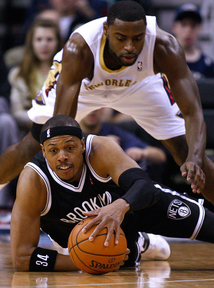 Photo - Brooklyn Nets forward Paul Pierce, bottom, and New Orleans Pelicans forward Tyreke Evans, top, go for a loose ball during the first half of an NBA basketball game in New Orleans, Monday, March 24, 2014. (AP Photo/Jonathan Bachman)