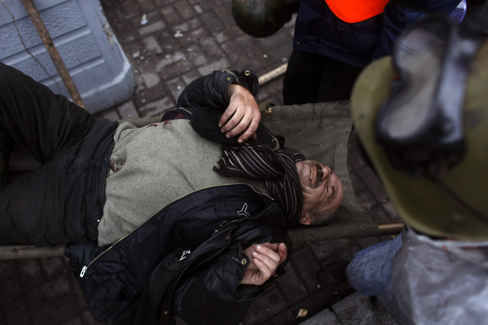 Photo - An injured anti-government protester is carried away to get treatment on the outskirts of Independence Square in Kiev, Ukraine, Thursday, Feb. 20, 2014. Fierce clashes between police and protesters, some including gunfire, shattered a brief truce in Ukraine's besieged capital Thursday, killing numerous people. The deaths came in a new eruption of violence just hours after the country's embattled president and the opposition leaders demanding his resignation called for a truce and negotiations to try to resolve Ukraine's political crisis. (AP Photo/Marko Drobnjakovic)
