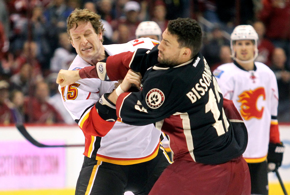 Photo - Calgary Flames right winger Tim Jackman, left, fights with Phoenix Coyotes left winger Paul Bissonnette, right, in the first period of an NHL hockey game Monday, Feb. 18, 2013, in Glendale, Ariz. (AP Photo/Paul Connors)