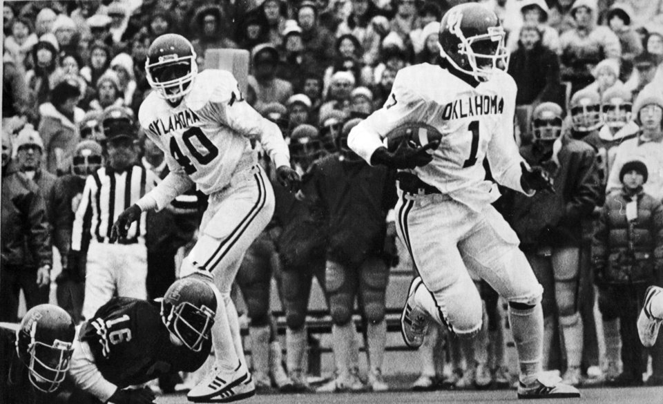 "FOOTBALL OU UNIVERSITY OF OKLAHOMA 1980 18.jpg: Caption reads ""As halfback Chet Winter (40) watches J.C. Watts turns a busted play into a 45-yard touchdown run to put the Sooners ahead to stay in the third period."" Photo taken by Jim Argo. Date photo was taken unknown. Photo was published in The Daily Oklahoman 10-26-1980."