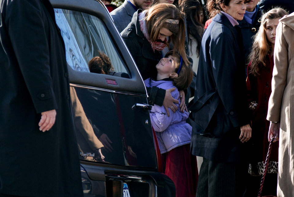 Photo - A child is embraced near a hearse carrying teacher Anne Marie Murphy, who was killed at the Sandy Hook Elementary School shootings in Newtown, after a funeral at St. Mary Of The Assumption Church  in Katonah, N.Y. Thursday, Dec. 20, 2012.  Newtown was killed when Adam Lanza, walked into Sandy Hook Elementary School in Newtown, Conn., Dec. 14, and opened fire, killing 26, including 20 children, before killing himself. (AP Photo/Craig Ruttle)