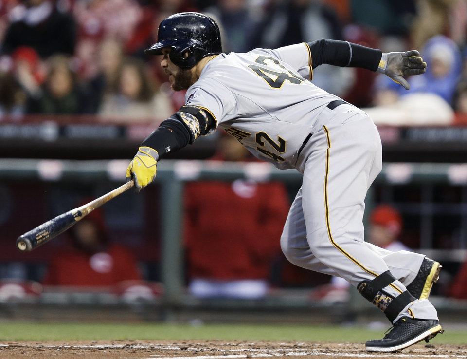 Photo - Pittsburgh Pirates' Russell Martin grounds into a fielder's choice against Cincinnati Reds starting pitcher Mike Leake to drive in a run in the fourth inning of a baseball game, Tuesday, April 15, 2014, in Cincinnati. (AP Photo/Al Behrman)