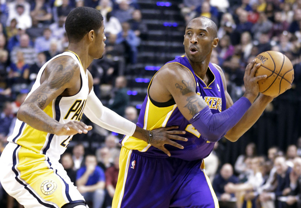 Photo - Los Angeles Lakers guard Kobe Bryant, right, looks to pass around Indiana Pacers forward Paul George in the first half of an NBA basketball game in Indianapolis, Friday, March 15, 2013.  (AP Photo/Michael Conroy)