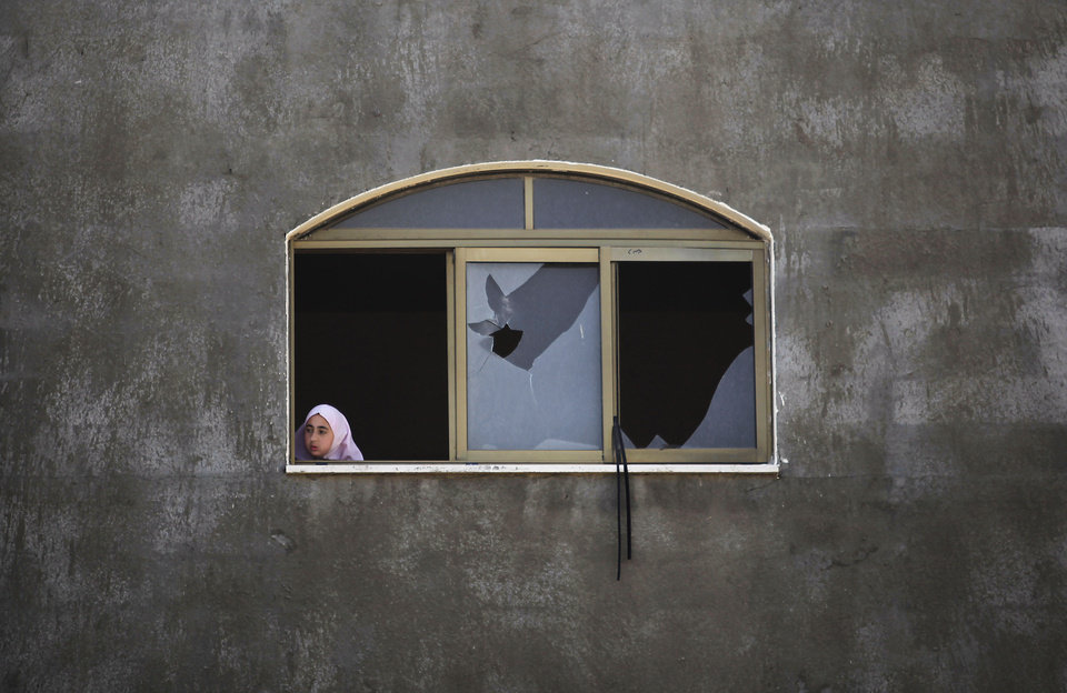 Photo - A Palestinian girl looks at a damaged home after it was hit by an Israeli missile strike in Gaza City, early Monday, June 16, 2014. Israel's military said it carried out airstrikes on five weapons and militant sites in Gaza, following overnight rocket fire from the coastal strip into Israel. Two rockets were intercepted and a third fell in an open area in Israel, causing no injuries, the military said. (AP Photo/Hatem Moussa)