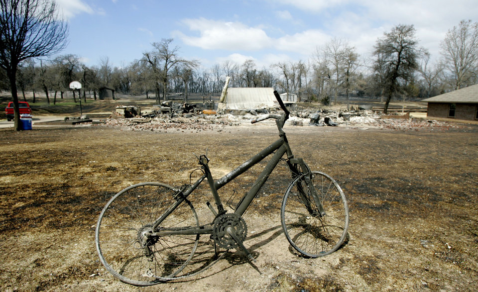 Photo - This bike is stands in the front lawn of 227 Pine Tree road that was destroyed in a wildfire in Choctaw, Oklahoma April 10, 2009.  Photo by Steve Gooch, The Oklahoman
