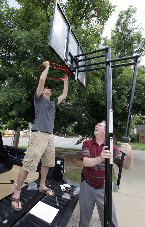 Photo -  J.J. Gourley, Westminster Presbyterian Church deacon, and Lee Cosby, Eagle Ridge community relations, put together a basketball goal donated to a family raising foster children. Photo by Paul B. Southerland, The Oklahoman   PAUL B. SOUTHERLAND -  PAUL B. SOUTHERLAND
