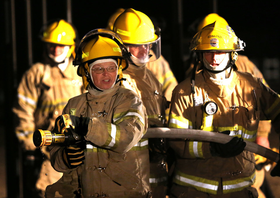 Photo - Regina Lowry waits for instructions during live firefighting training Nov. 15 at the Edmond Fire Department's Citizens Fire Academy. PHOTOS BY SARAH PHIPPS, THE OKLAHOMAN