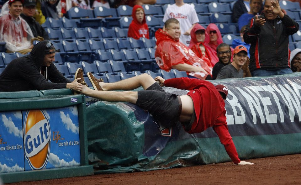 Photo - A fan is pulled back into the stands after falling onto the field while chasing a foul ball by Philadelphia Phillies' Marlon Byrd during the fourth inning of a baseball game against the San Diego Padres, Thursday, June 12, 2014, in Philadelphia. (AP Photo/Matt Slocum)