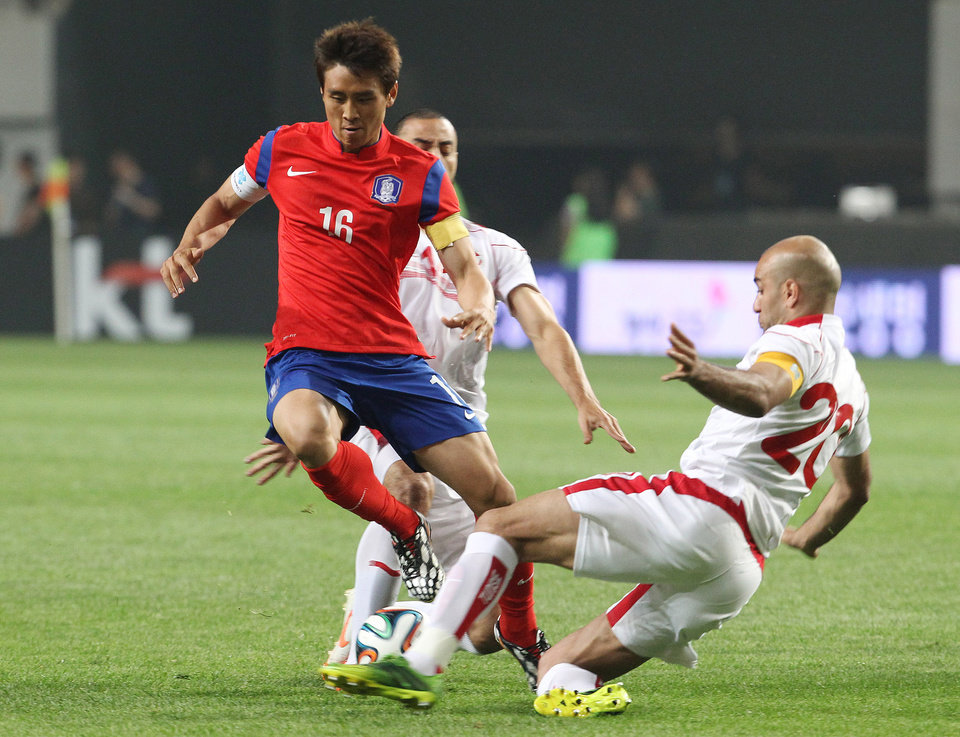 Photo - South Korea's Koo Jacheol, left, fights for the ball against Tunisia's Stephane Houcine Nater and Aymen Abdennour, right, during their friendly soccer match at World Cup stadium in Seoul, South Korea, Wednesday, May 28, 2014. South Korea will play against Belgium, Russia and Algeria in Group H of the World Cup 2014 in Brazil. (AP Photo/Ahn Young-joon)