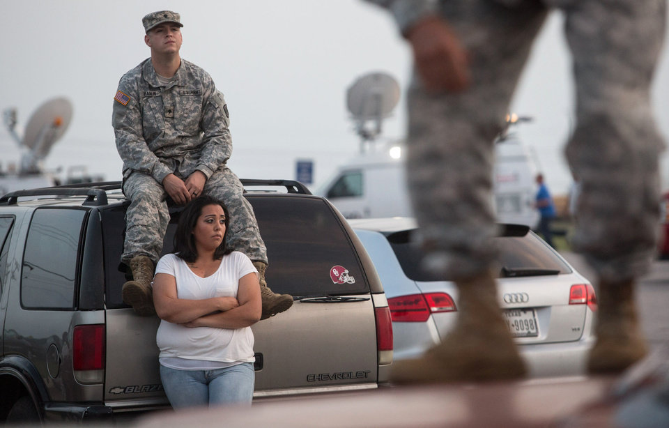Photo - Lucy Hamlin and her husband, Spc. Timothy Hamlin, wait for permission to re-enter the Fort Hood military base, where they live, following a shooting on base on Wednesday, April 2, 2014, in Fort Hood, Texas. One person was killed and 14 injured in the shooting, and officials at the base said the shooter is believed to be dead. The details about the number of people hurt came from two U.S. officials who spoke on condition of anonymity because they were not authorized to discuss the information by name. (AP Photo/ Tamir Kalifa)