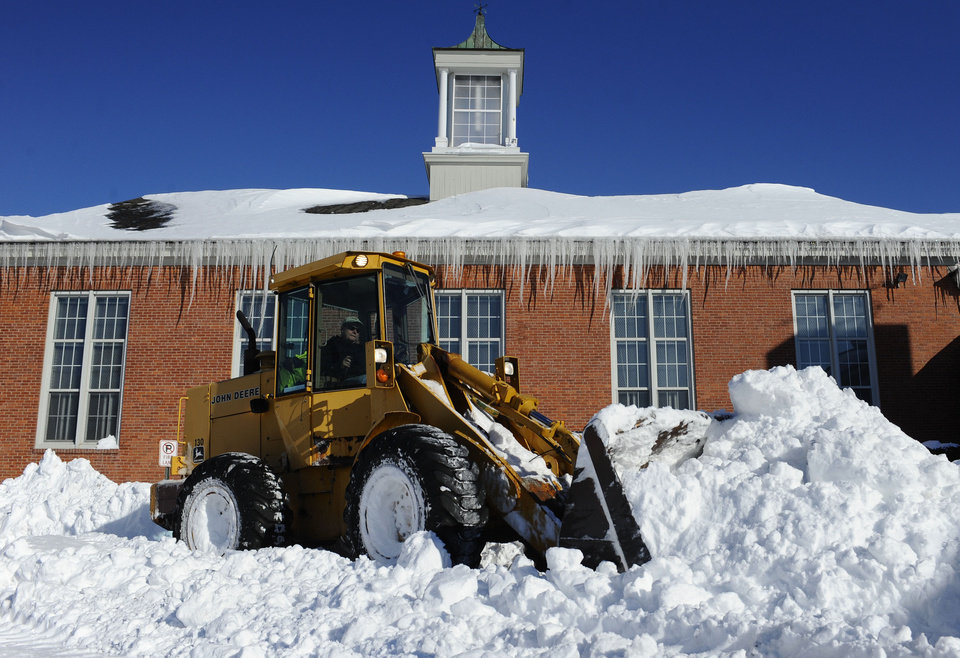 Photo - A plow clears a path outside Poquonock Elementary School in Windsor, Conn., Sunday, Feb. 10, 2013.  A howling storm across the Northeast left much of the New York-to-Boston corridor covered with more than three feet of snow on Friday into Saturday morning. (AP Photo/Jessica Hill)