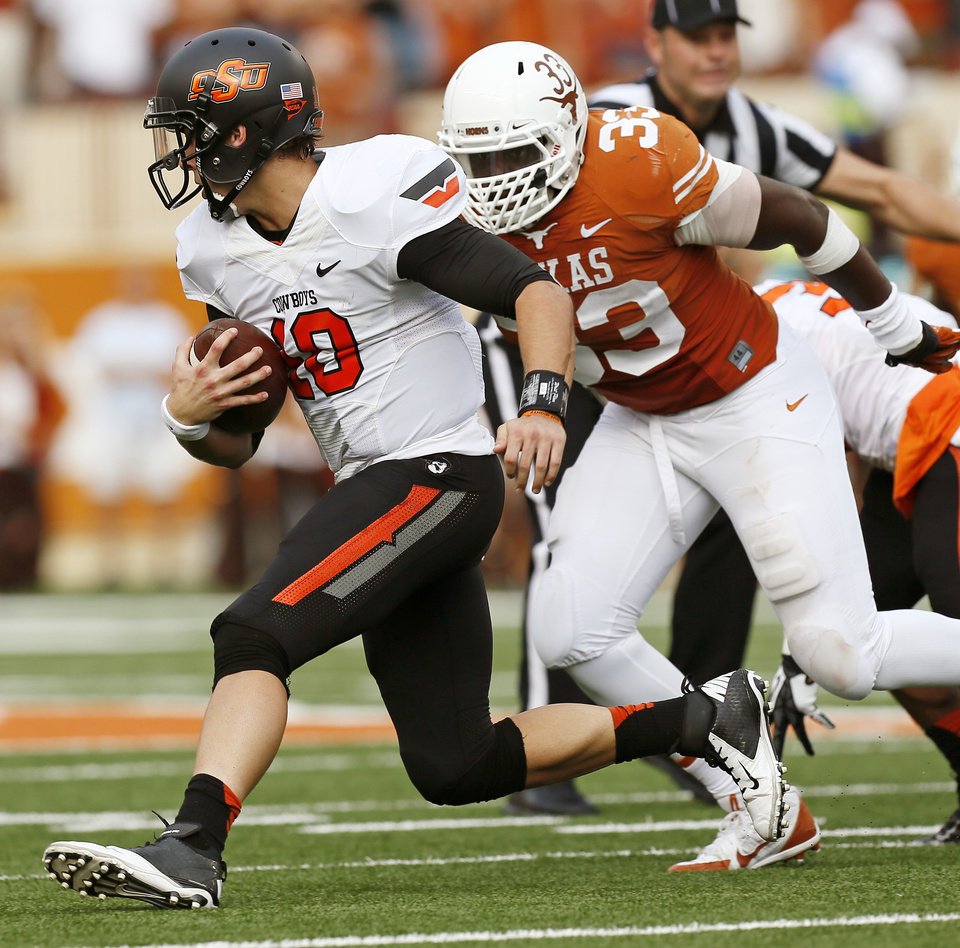 Oklahoma State's Clint Chelf (10) carries the ball away from UT's Steve Edmond (33) during a college football game between the Oklahoma State University Cowboys (OSU) and the University of Texas Longhorns (UT) at Darrell K Royal - Texas Memorial Stadium in Austin, Texas, Saturday, Nov. 16, 2013. Photo by Nate Billings, The Oklahoman