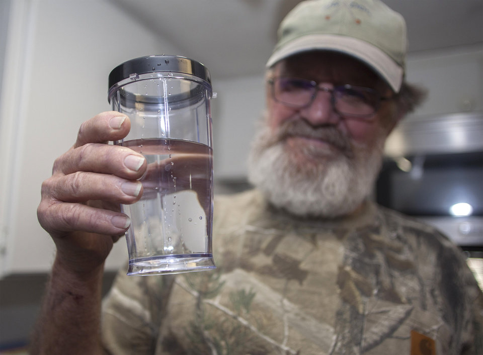 """Photo - Flemington Road community member Sam Malpass of Wilmington, N.C. holds a glass of water from his home on Wednesday, Feb. 19, 2014. Malpass and his wife Pat are part of a small community near L.V. Sutton Complex operated by Duke Energy they feel could be polluting well water with spill off and seepage from large coal ash ponds. """"If you want to know what it's like living near a coal ash pond, this is it,"""" said Malpass, 67, a retired carpenter and Vietnam veteran. """"We're afraid to drink the water because we don't know what's in it. We can't eat the fish because we don't know if it's safe anymore. It's changed our lives out here.""""   (AP Photo/Randall Hill)"""