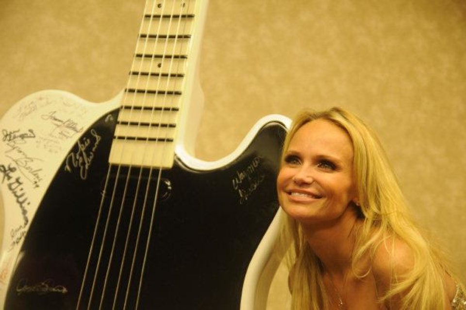 Singer and actress Kristin Chenoweth smiles after signing the oversized Oklahoma Music Hall of Fame guitar at her induction into the hall of fame on Thursday in Muskogee. Photos by Adam Kemp, For The Oklahoman